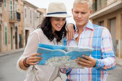 Young couple of tourists consulting a map. Trendy attractive young couple of tourists consulting a map as they search for their destination while out sightseeing Royalty Free Stock Photos