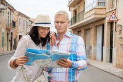 Young couple of tourists consulting a map. Trendy attractive young couple of tourists consulting a map as they search for their destination while out sightseeing Stock Photos