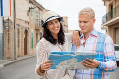 Young couple of tourists consulting a map. Trendy attractive young couple of tourists consulting a map as they search for their destination while out sightseeing Stock Photography