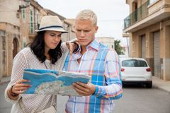 Young couple of tourists consulting a map. Trendy attractive young couple of tourists consulting a map as they search for their destination while out sightseeing Royalty Free Stock Image