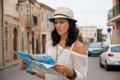 Young couple of tourists consulting a map. Trendy attractive young couple of tourists consulting a map as they search for their destination while out sightseeing Stock Image