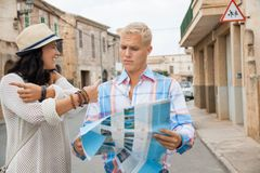 Young couple of tourists consulting a map. Trendy attractive young couple of tourists consulting a map as they search for their destination while out sightseeing Royalty Free Stock Photo