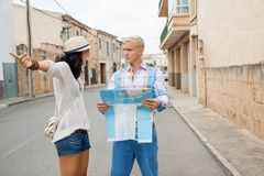 Young couple of tourists consulting a map Royalty Free Stock Photo