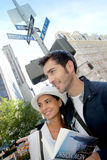 Young couple of tourists in crossroads. Tourists on Broadway street reading city guide Royalty Free Stock Image