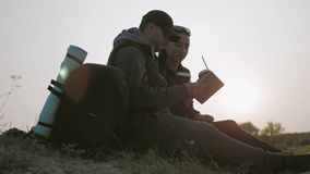A young couple of tourists enjoy a tablet sitting on top of a mountain during sunset. A young couple of tourists enjoy a tablet sitting on top of a mountain stock video