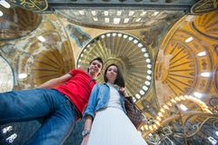 Young couple tourists inside the Blue Mosque on a Royalty Free Stock Photo