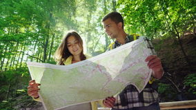 A young couple of tourists looking at a map. They stand in the rays of the sun in the forest near the waterfall