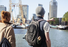 Young couple tourists looking and pointing to Rotterdam city harbour, future architecture concept, industrial lifestyle Stock Image