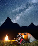 Young couple tourists looking to the shines starry sky and Milky way in the camping at night near campfire Stock Photos