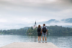 Young couple of tourists in love on the Lake Bled, Slovenia. Young couple of tourists in love standing on a wooden pier on the background with Bled Castle and royalty free stock photography