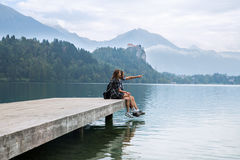 Young couple of tourists in love on the Lake Bled, Slovenia. Young couple of tourists in love standing on a wooden pier on the background with Bled Castle and stock photos
