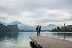 Young couple of tourists in love on the Lake Bled, Slovenia. Young couple of tourists in love standing on a wooden pier on the background with Bled Castle and stock images