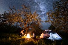 Young couple tourists sitting at a campfire near tent under trees and beautiful night sky full of stars and milky way. Night camping. Long exprose Royalty Free Stock Image