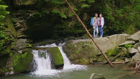 A young couple of tourists are standing near a waterfall on a mountain river. Admire the beautiful scenery. Tourism and