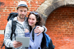 Young couple of tourists using tablet to visit city Royalty Free Stock Images