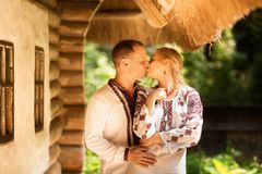 Young couple in traditional Ukrainian clothes kissed on the background of old ukrainian architecture.  stock image
