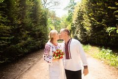 A young couple in a traditional Ukrainian clothing whith bouquet walking and kissing in the sunny park royalty free stock photos