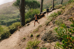 Young couple trail running on a mountain path. Stock Images