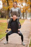 A young couple is training in an autumn park. The guy is holding the girl on his shoulders and crouching. Young happy loving couple practicing in autumn park Stock Photography