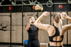 Young couple training with ball in the crossfit gym. Young athletic couple in blacksportswear training with crossfit wall ball in the gym royalty free stock photos