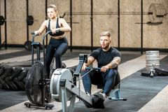 Couple training with exercise machines in the gym Stock Photo