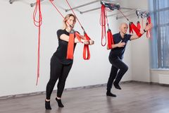 Young couple training on a ropes and straps at the clinic. stock image