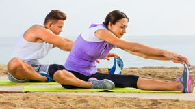Young couple training yoga poses sitting on beach Royalty Free Stock Photography