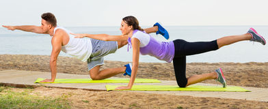Young couple training yoga poses sitting on beach Royalty Free Stock Image