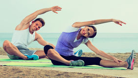 Young couple training yoga poses sitting on beach Royalty Free Stock Photos