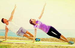 Young couple training yoga poses sitting on beach Stock Images