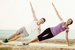 Young couple training yoga poses sitting on beach Stock Photography