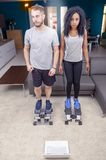Young couple he trains with the step machine at home. In a modern apartment Stock Photo