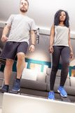 Young couple he trains with the step machine at home. In a modern apartment Stock Images