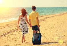 Young couple with travel bag on the beach Stock Photography