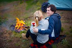 Young couple traveler sitting by the fire and drinking tea royalty free stock images