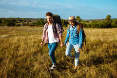 Young couple of travelers with backpacks smiling, walking in field. Young beautiful couple of travelers with backpacks smiling, walking in field. Copy space Stock Photos