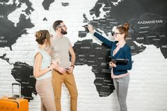 Couple with travel agent at the office. Young couple of travelers choosing a summer trip with travel agent pointing on Great Britain on the world map Stock Images