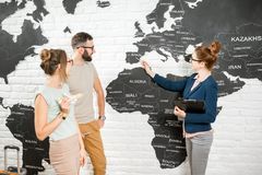Couple with travel agent at the office. Young couple of travelers choosing a summer trip with travel agent pointing on Spain on the world map Stock Photos