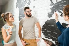 Couple with travel agent at the office. Young couple of travelers choosing a summer trip with travel agent pointing on the world map Royalty Free Stock Images