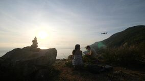Young couple travelers flying drone at a mountain sea cliff.