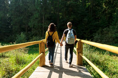 Young couple of travelers going on wooden bridge in mountains. Young beautiful couple of travelers with backpacks going on wooden bridge in mountains. Copy Royalty Free Stock Photography