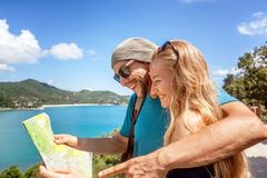 A young couple of travelers look in the map, sea and a beautiful Royalty Free Stock Image