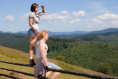 Young couple of travelers. Looking around mountain countryside summer view Royalty Free Stock Images