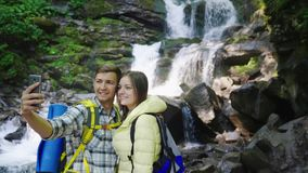 A young couple of travelers photographing themselves against the background of a waterfall in the mountains. Crane shot. A young couple of travelers stock video footage