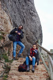 Young couple travelers stopped to rest before climbing a mountain Royalty Free Stock Image