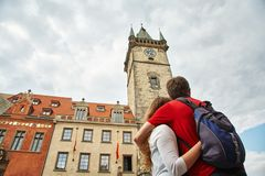 Young couple travelers walking on a street of European city. sightseeing in Prague, Czech Republic, Old Town Hall. royalty free stock image