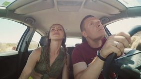 Young couple traveling in the car through the rocks. Man and woman have fun, making funny face on the road together stock video footage