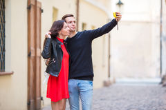 Young couple traveling on holidays in Europe smiling happy. Caucasian family making selfie in european empty old streets. Happy tourist couple, men and women royalty free stock images