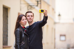 Young couple traveling on holidays in Europe smiling happy. Caucasian family making selfie in european empty old streets. Happy tourist couple, men and women royalty free stock image