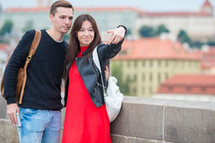 Young couple traveling on holidays in Europe smiling happy. Caucasian family making selfie in popular Karlov Most. Happy tourist couple, men and women traveling stock photography